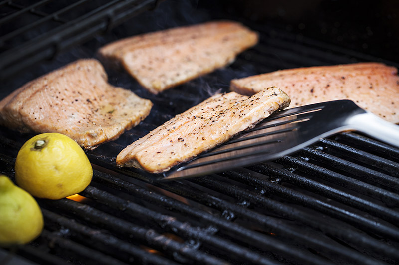 With the spatula turned upside down and providing pressure to the grill, gently nudge the fish clear from the gridiron. Do not use excessive force or you will end up breaking the fish. The movement should be gentle and the fish will come lose from the grill when it's ready. Don't force it.