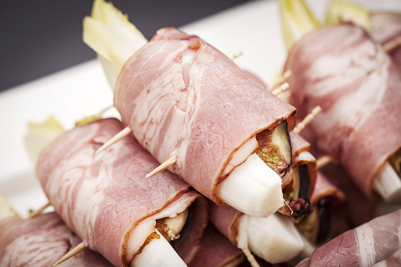 Wrap the bacon around the asparagus and hold it in place with tooth picks. Cut each endive in half, pair it with a quarter of fresh fig, apple or pear, wrap with bacon and secure with tooth picks.