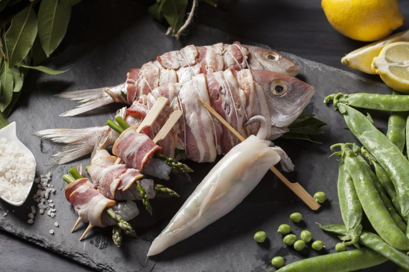 Here's what you'll finish up with, ready for the grill. Snapper stuffed with bay, parsley, lemon and onion, wrapped in bacon and tied of with string. Prawns and asparagus wrapped in bacon and skewered and calamari stuffed stuffed with bacon, leek and green peas.