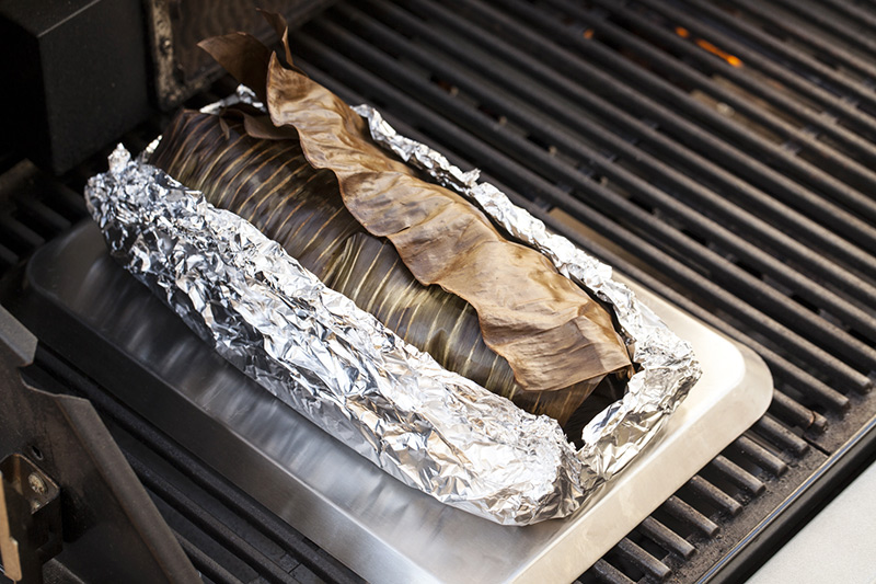 Then, using a heavy gauge aluminium foil, form a tight pocket around the leaves to keep them closed. Because we won't be using burlap and sand to hold everything together, the foil helps to keep everything intact while it cooks. Turn on one side of the barbecue to medium-high and on the opposite side of the place a baking tray upside down with the roast on top. This will mimic the contact from the rocks it would normal come into contact with in an Imu. (Don't use a cast-iron hotplate for this exercise as it won't get hot enough over indirect heat.).